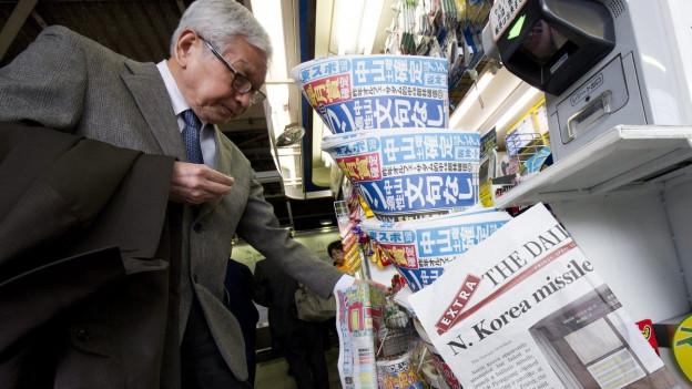 Ein ältere Mann in Anzug, den Mantel über dem Arm, graue Haare und mit Brille, steht in Japan an einem Kiosk, im Vordergrund sind verschiedenen Zeitungen zu sehen (2012).