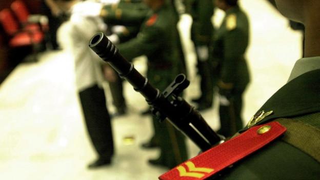 Ein chinesischer Polizist mit einem Gewehr beobachtet eine Hinrichtung im Jahr 2002.