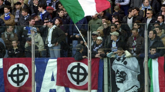 Lazio Rom Fans zeigen bei einem Fussballspiel Faschisten-Flaggen und Mussolinie-Porträts.