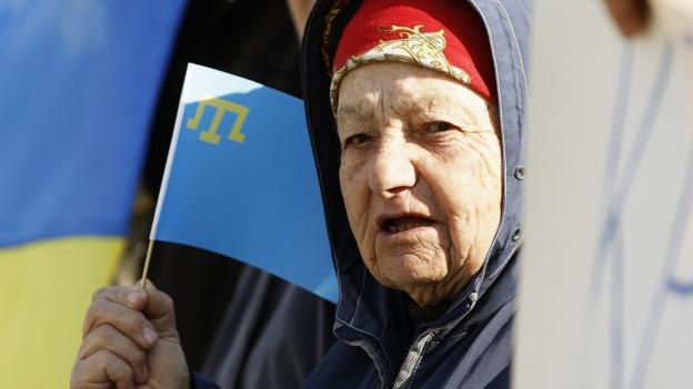 Alte Frau mit einer Fahne der Krim-Tataren.