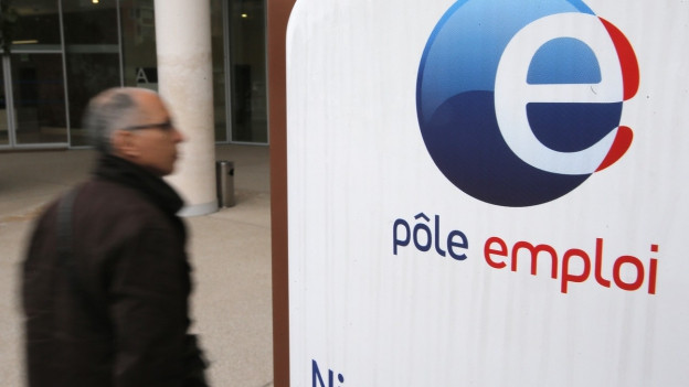 Ein älterer Herr mit grauem Haar läuft an einem weissen Schild vorbei. Darauf steht in blauer und roter Schrift «Pôle Emploi».