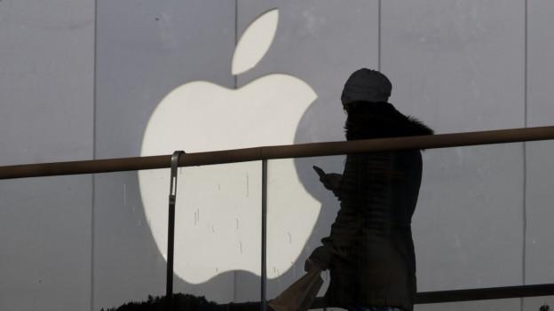 Eine Passantin geht an einem Apple-Shop vorbei.