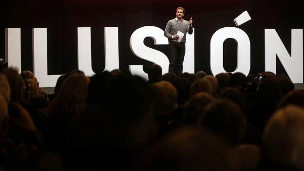 Ein Politiker steht auf einer Bühne, hunderte Menschen davor. Hinter ihm steht der Schriftzug «Illusion» auf Spanisch geschrieben.