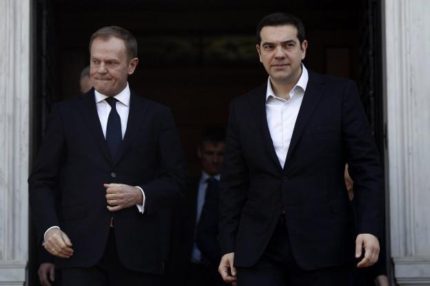 EU-Ratspräsident Tusk (links) und der griechische Ministerpräsident Tsipras (rechts) bei einem früheren Treffen in Athen, sie verlassen beide ein Gebäude und tragen dunkle Anzüge, schauen ernst (3. März 2016).