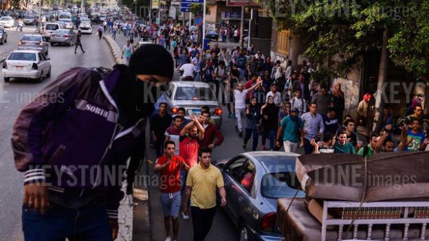 Ein Protestmarsch in der ägyptischen Hauptstadt Kairo. Im Vordergrund ein vermummter junger Mann.
