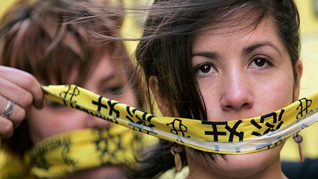 Zwei Freiwillige von Amnesty International halten sich einen mit chinesischen Schriftzeichen bedruckten gelben Schal vor den Mund.