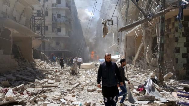 Eine Strasse voller Trümmer, im Hintergrund zerstörte Wohnblocks, im Vordergrund schreiten zwei Männer über die Trümmer.