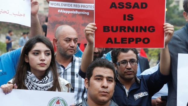Menschen prangern mit Plakaten Angriffe auf syrische Stadt Aleppo an.