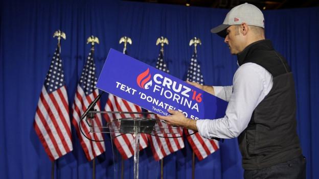 Ein Wahlkampfhelfer hält Kartonschilder in der Hand, die für Ted Cruz werben.