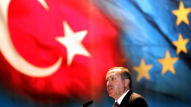 Der türkische Präsident Erdogan steht vor einer türkischen und einer EU-Flagge.
