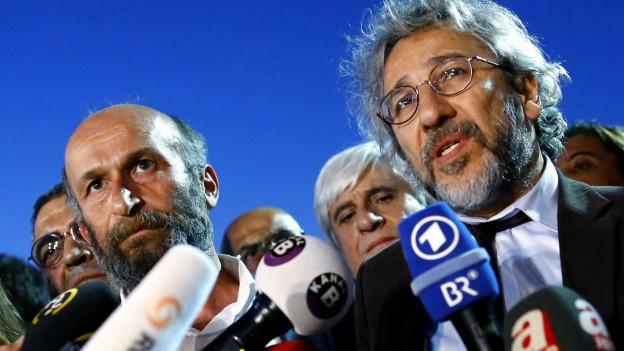 Can Dunda und Erdem Gül vor einer Vielzahl von Reportermikrofonen.