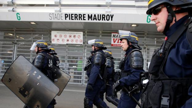 Polizisten mit Helmen und Schilden vor einem Stadion.
