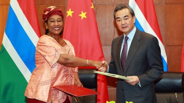 Die Aussenministerin von Gambia schüttelt vor dem Hintergrund beider Länderflaggen die Hand ihres chinesischen Amtskollegen.