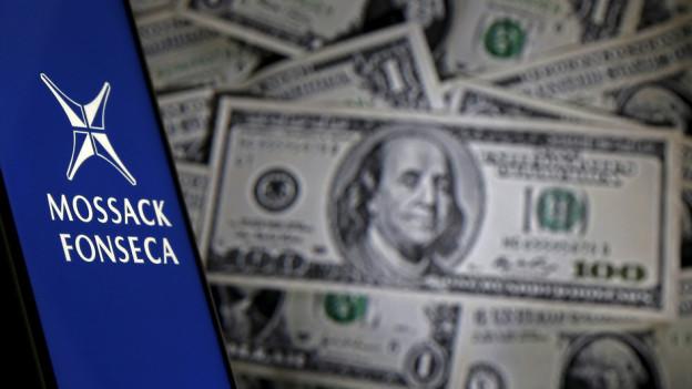 Bildmontage aus dem Logo von Mossack Fonseca und mehreren hundert Dollar Noten im Hintergrund.