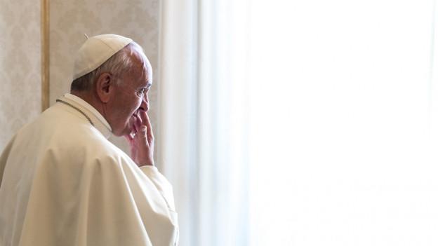 Papst Franziskus blickt in Gedanken vertieft von der Kamera weg und zu einem Fenster hinaus.
