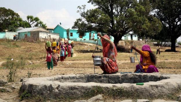 Eine dürre Landschaft, im Vordergrund ein Brunnen, auf dessen Mauern zwei Frauen am Wasserholen sind.