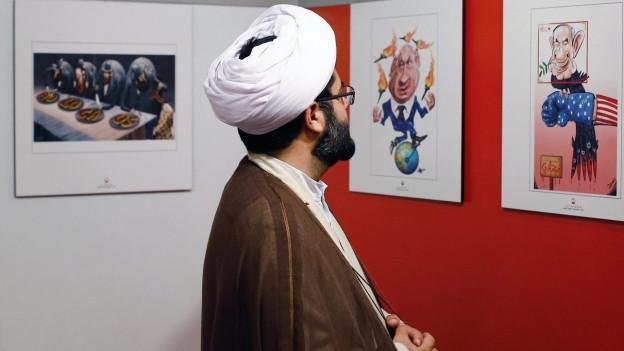 Ein iranischer Kleriker in der Ausstellung von Holocaust-Cartoons.