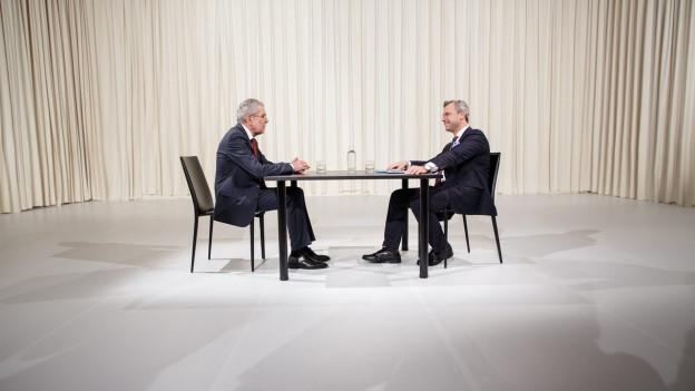 Alexander Van der Bellen und Norbert Hofer sitzen in einem Fernsehstudio an einem Tisch vor einem beigefarbenen Vorhang.