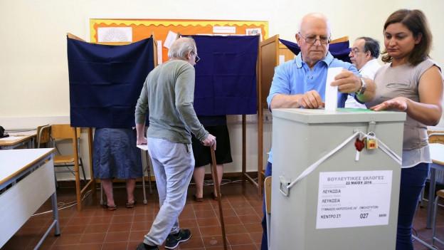 Ein Wahllokal in Zypern, mehrere Menschen werfen ihre Wahlzettel ein.