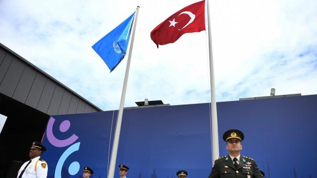 Die Flaggen der UNO und der Türkei wehen nebeneinander, darunter stehen einige Soldaten.
