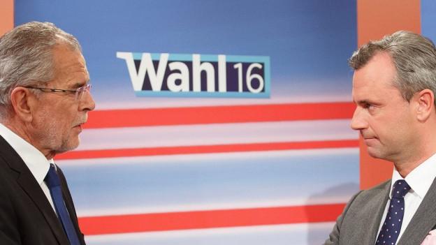 Die Kandidaten van der Bellen (links) und Hofer (rechts) vor einer blauen Wand, auf der «Wahl 16» zu lesen ist.
