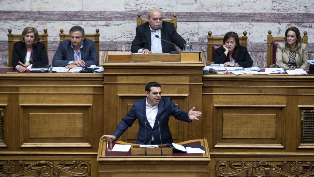 Der griechische Ministerpräsident spricht am Rednerpult im Parlament. Hinter ihm sitzen Abgeordnete mit frustrierten bis gelangweilten Gesichtern.
