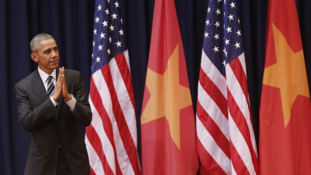 Präsident Obama steht in der linken Bildhälfte, die Hände aneinander gelegt und den Kopf geneigt. Neben ihm sind die amerikanische und die vietnamesische Flagge zu sehen.