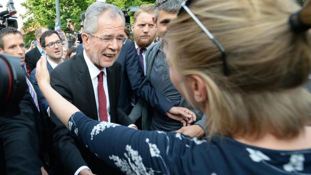 Der neue österreichische Bundespräsident umarmt eine Frau, die von rechts ins Bild kommt. Van der Bellen lächelt und streckt die Arme aus.