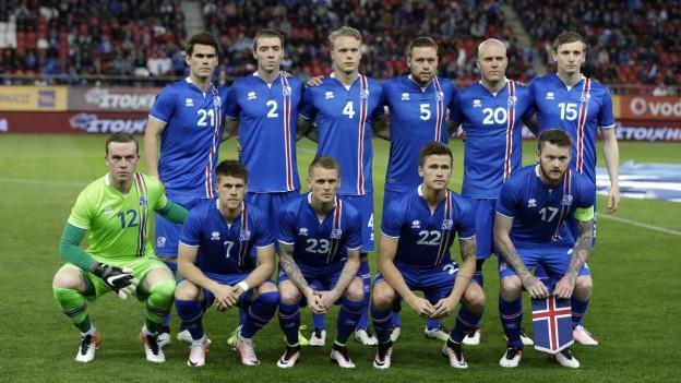 Auf dem Bild ist die Fussball-Nationalmannschaft in einem Stadion zu sehen. Sie tragen blaue Trikots.