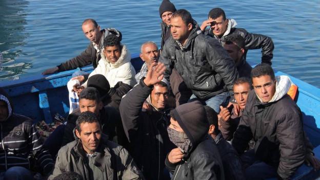 Zu sehen ist ein Boot im Wasser, in dem sich mehrere junge Männer aus den Mahgreb-Staaten befinden.
