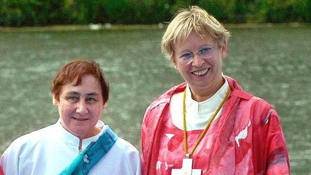 Zu sehen ist Christine Mayr-Lumetzberger links, in roter Bischofstracht, daneben eine Frau in weisser Kleidung.