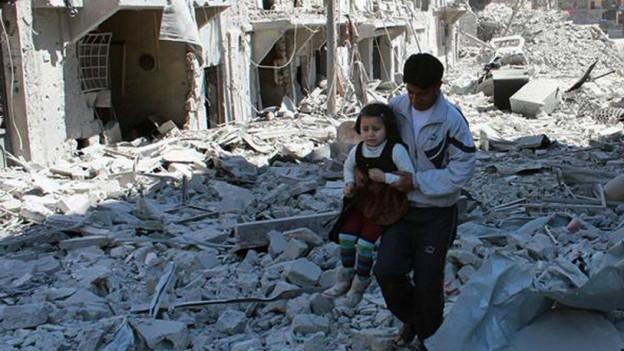 Der Krieg geht weiter: Ein Mann trägt ein kleines Mädchen durch die Trümmer von Aleppo (21. April 2014).