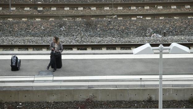 Eine Frau wartet auf dem Perron auf ihren Zug.