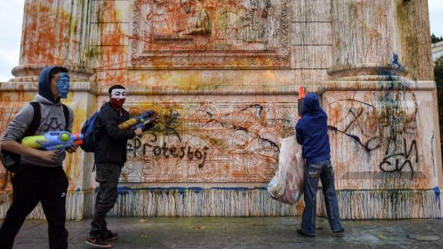 Demonstranten benutzen Wasserpistolen, um Fassaden bunt zu besprühen.