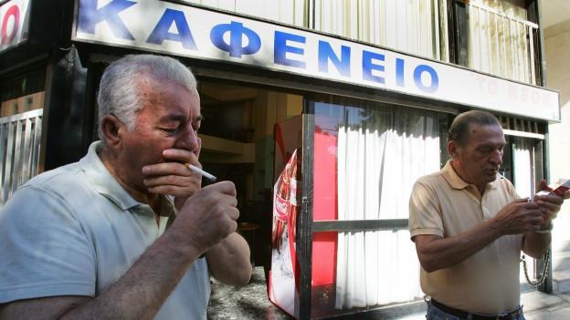 Zwei ältere Männer zünden sich vor einem Athener Café eine Zigarette an.