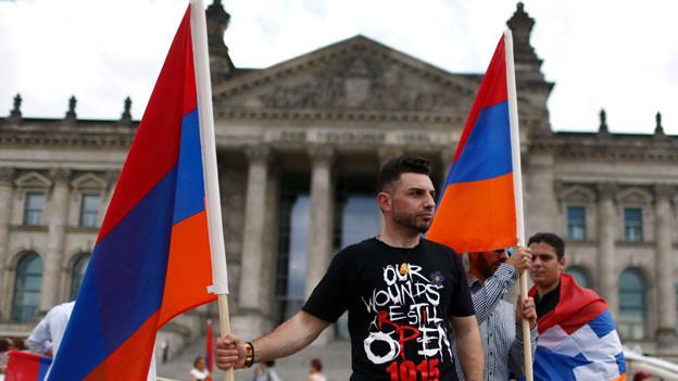 Ein Demonstrant mit armenischen Flaggen vor dem Reichstag, dem Sitz des Bundestags in Berlin.