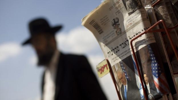 Orthodoxer Jude im Hintergrund, davor eine israelische Zeitung an einem Kiosk