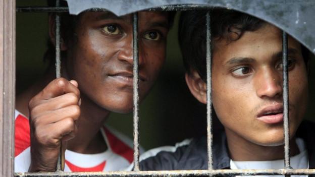 Zwei junge Flüchtlinge,Angehörige der burmesischen Minderheit der Rohingya, blicken durch ein vergittertes, zerbrochenes Fenster.