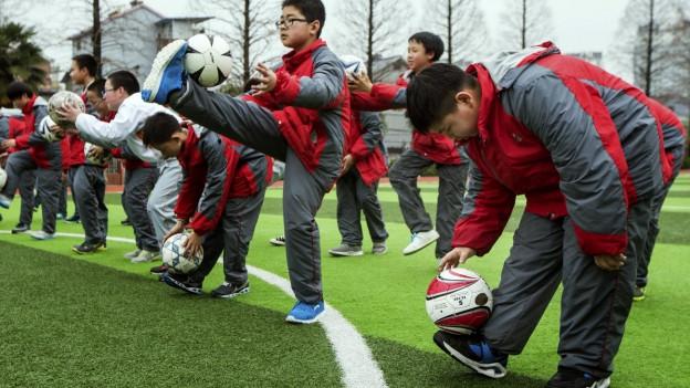 Chinesische Kinder üben sich im Fussballspielen