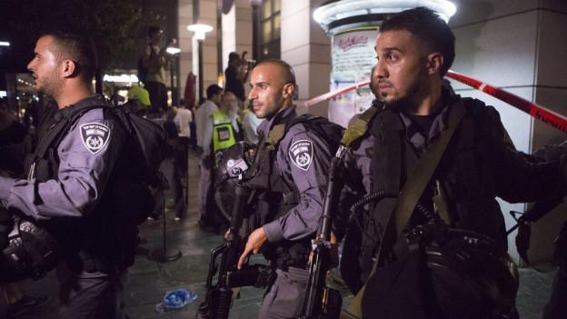 Schwer bewaffnete Polizisten vor einer Absperrung.