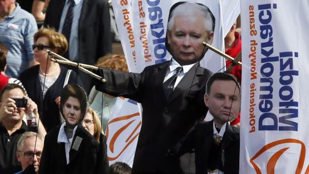 Eine Demonstration in Warschau gegen die PIS mit Transparenten.