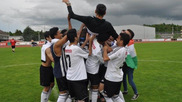 Im Siegesjubel lassen die jungen Spieler den Trainer hochleben.