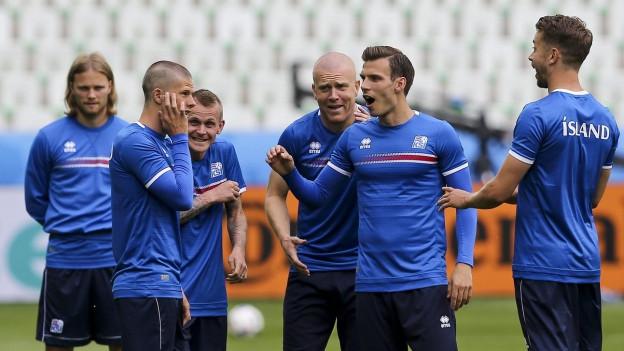 Mehrere Spieler der Isländischen Fussballnationalmanschaft stehen auf dem Trainingsplatz in Frankreich und unterhalten sich angeregt.