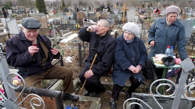 Russen trinken Wodka auf einem Friedhof.