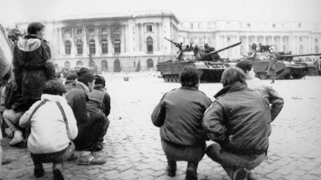 Weihnachtsabend 1989: Rumäninnen und Rumänen beobachten die Panzer vor dem Königspalast in Bukarest.