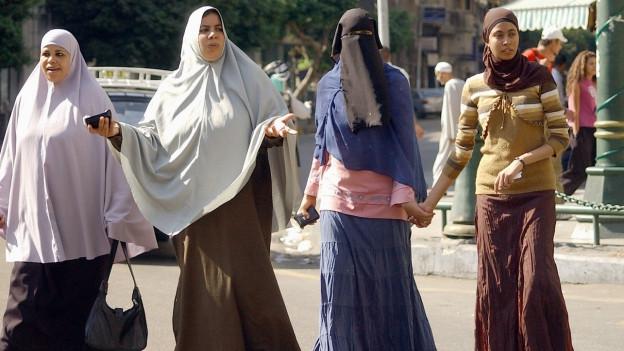 Mehrere muslimische Frauen, mehr oder weniger verhüllt, überqueren eine Strasse in Kairo.
