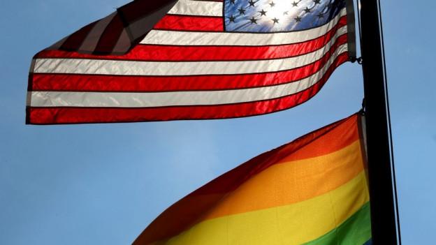 Eine Regenbogenfahne und eine amerikanische Fahne wehen im Wind.