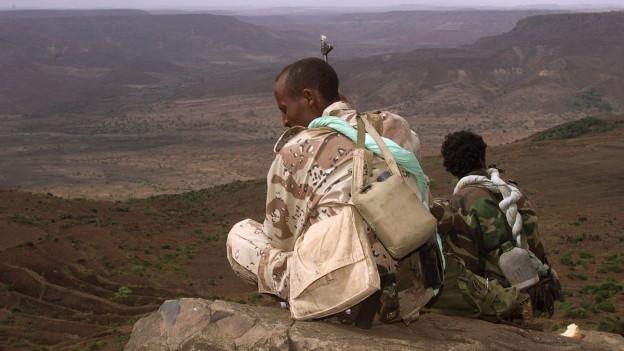 Eritreische Soldaten beobachten die Front von der Spitze einer Klippe im Mai 2000.
