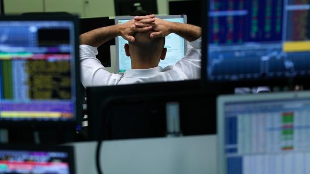 Ein Aktienhändler umgeben von Computern und Aktienkursen.