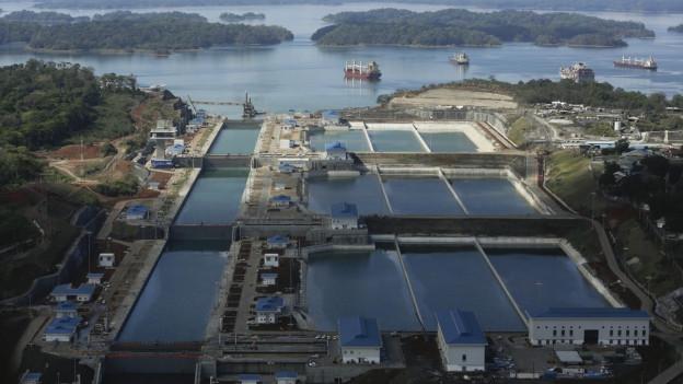 Eine Luftaufnahme des Erweiterungsbaus am Panama-Kanal, man sieht den Kanal und verschiedene Betonmauern..